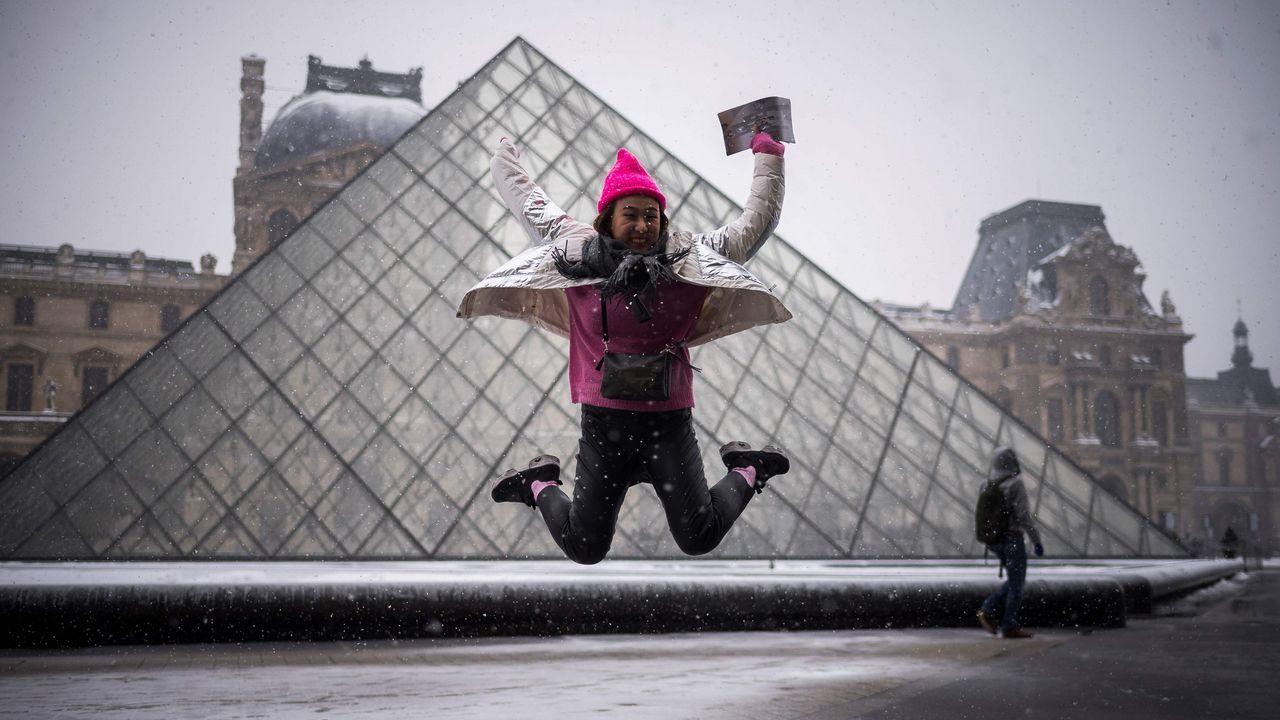 Un turista salta frente al Louvre, en París