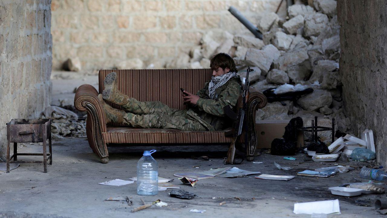 Un soldado del Ejercito sirio consulta su móvil mientras descansa en un sofá
