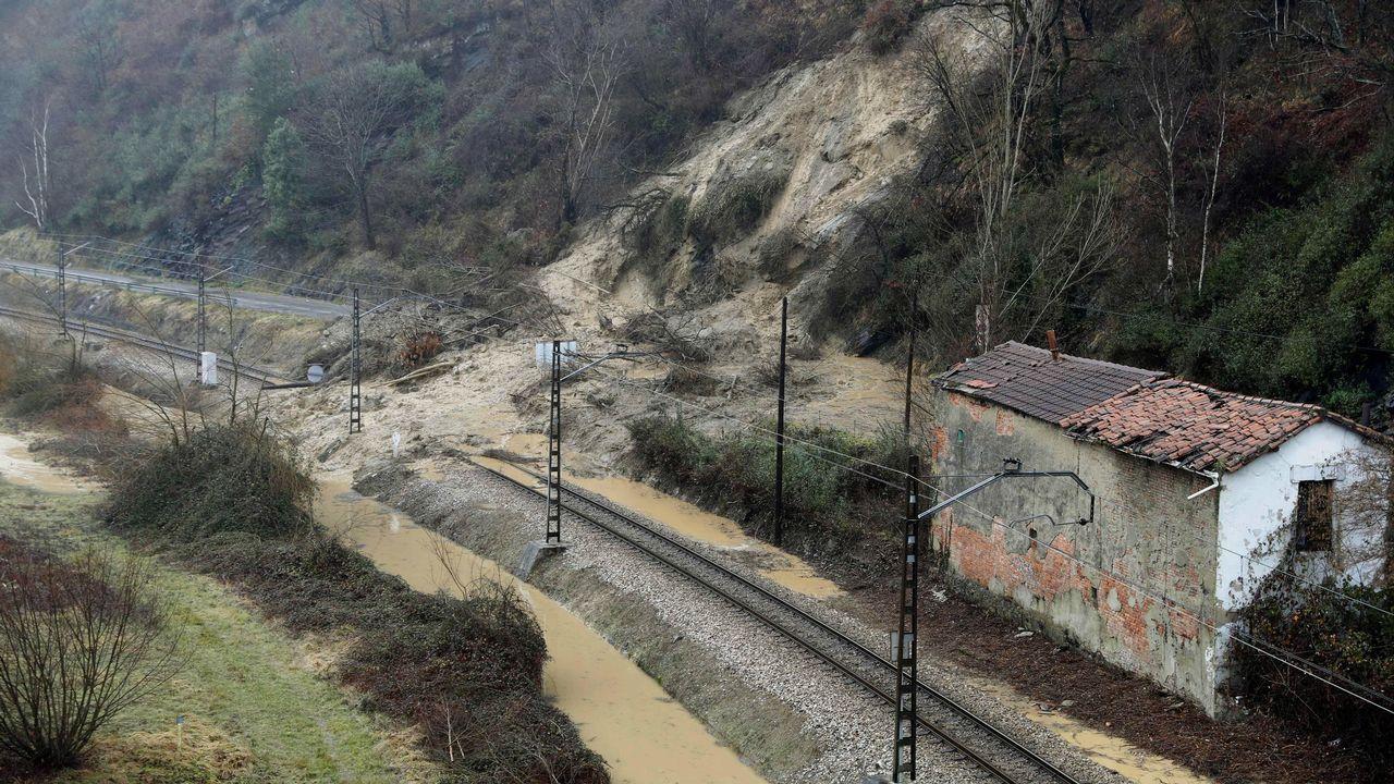 Aspecto que presenta la vía de tren y la carretera comarcal a su paso por Laviana a causa del temporal de lluvias registrado en los últimos días en Asturias