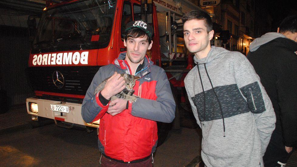 Marcos Rodríguez y Nacho San Bartolomé, con su gata Nika después de que se la entregasen los bomberos