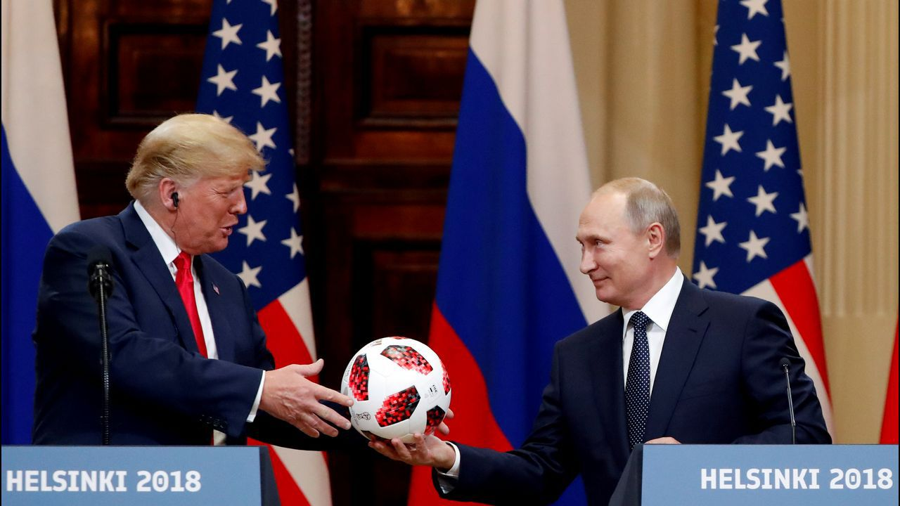 Vladimir Putin entrega un balón de fútbol a Donald Trump durante la cumbre de Helsinki