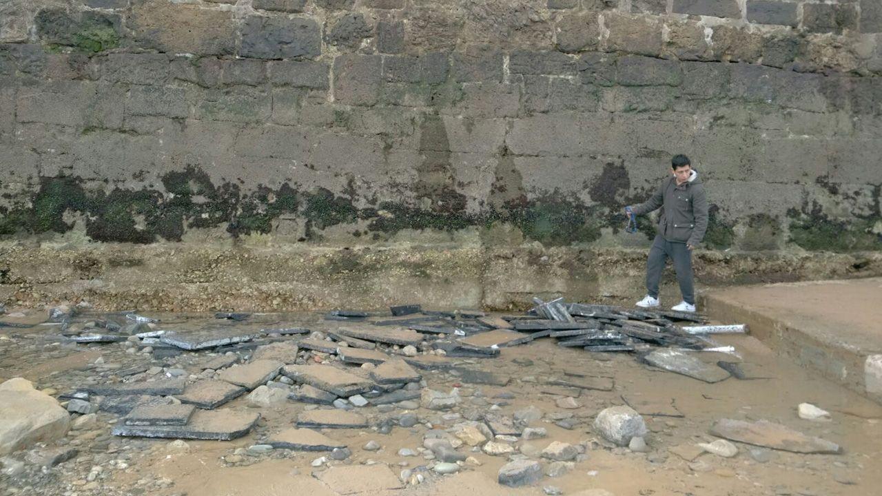 Vista aérea de La Providencia, enla costa de Gijón.Un chico observa la falta de arena en la playa de San Lorenzo junto a la escalerona