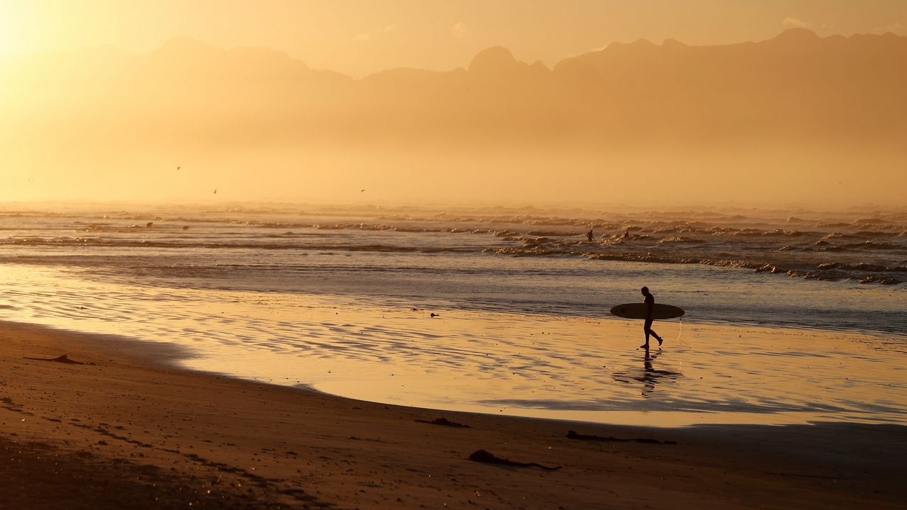 Un surfista sudafricano pasea al amanecer en la playa Muizenberg en Ciudad del Cabo (Sudáfrica).