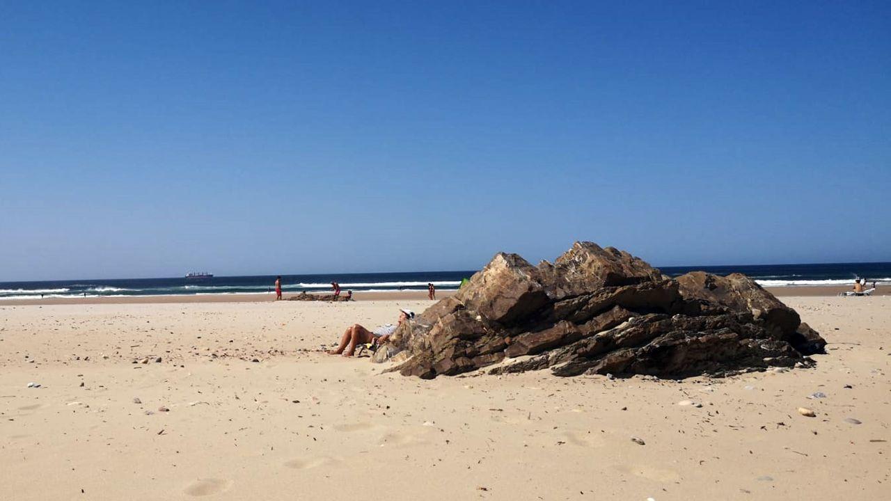 Una bañista se protege del vientro detrás de una piedra en la playa de Xagó (Gozón)
