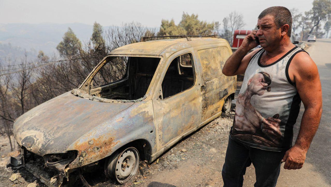 Un residente habla por teléfono junto a su furgoneta calcinada por los incendios declarados en Monchique, Algarve, sur de Portugal