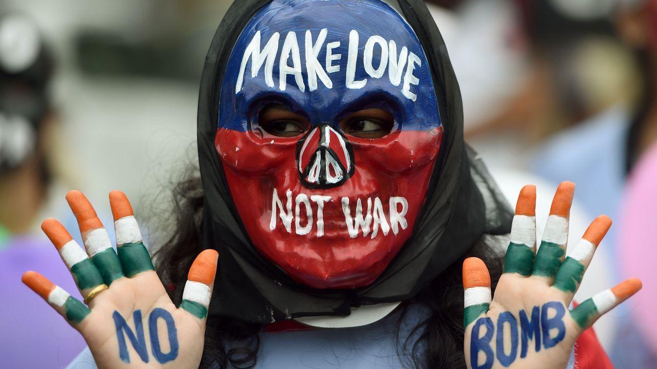 Una estudiante india con una máscara posa con sus manos pintadas con lemas de paz durante un mitin para conmemorar el Día de Hiroshima