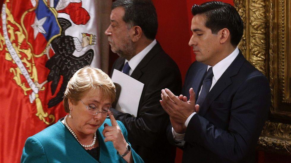 La presidenta Michelle Bachelet pasa junto al ex ministro del Interior Rodrigo Peñalillo (dcha.) y el subsecretario de Relaciones, Mahmoud Aleuy (centro)