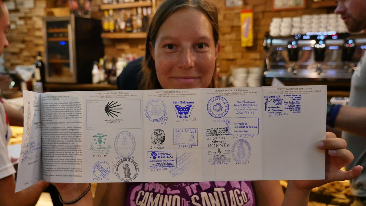 Julia nos enseña su credencial llena de sellos en Arzúa
