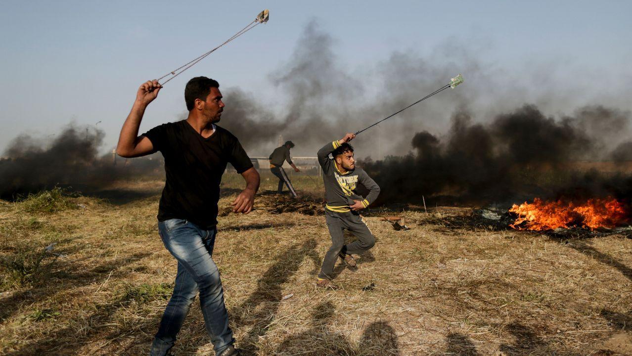 Dos palestinos lanzan piedras durante las protestas contra el ejército israelí, en Gaza