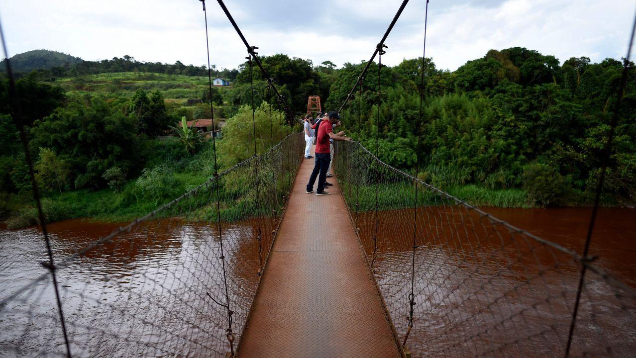 La gente mira el río Paraopeba afectado por el lodo, un día después del derrumbe de la represa