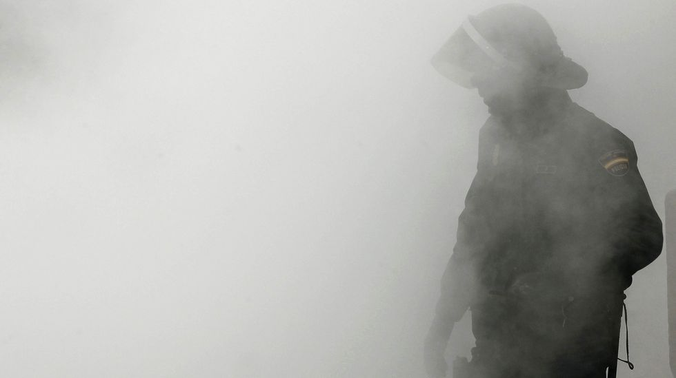 Un policía nacional envuelto en el humo provocado por la quema de un contenedor, durante un incidente ocurrido en Pamplona en el 2013