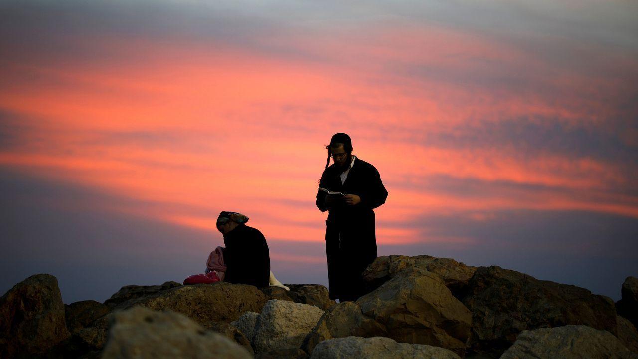 Un judío ultraortodoxo reza al atarceder en la ciudad israelí de Ashkelon