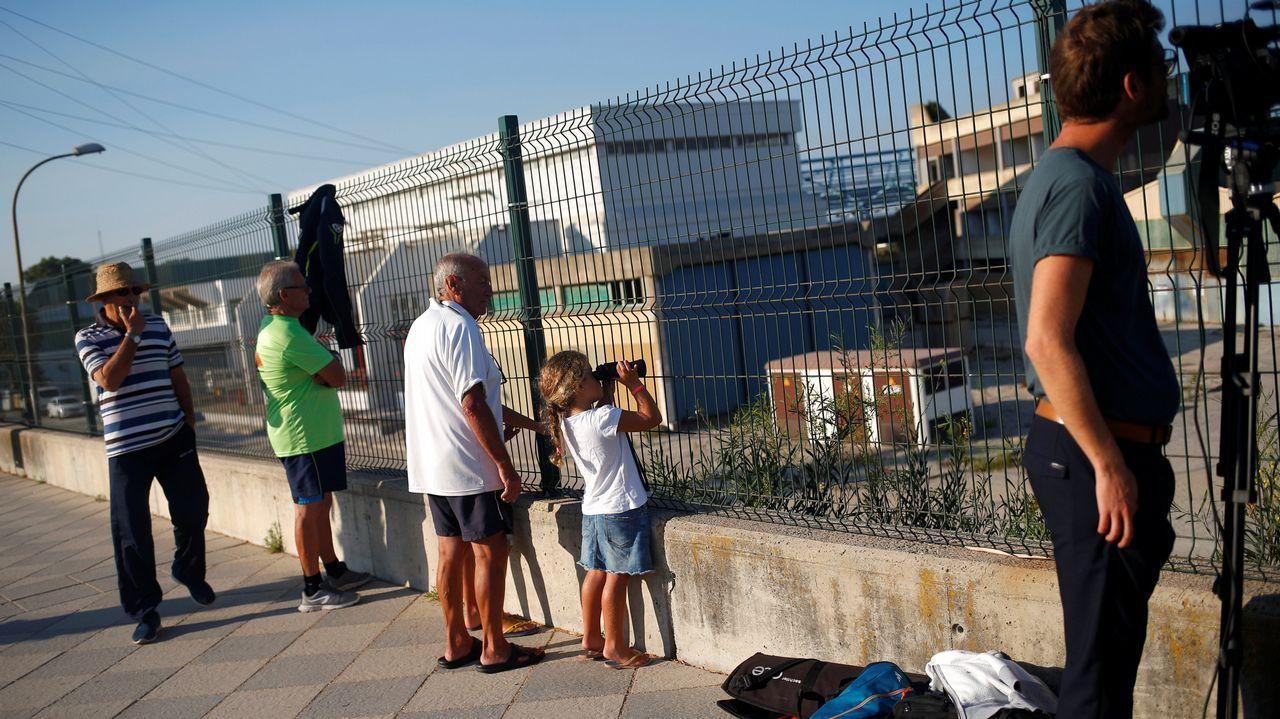 .Una niña usa binoculares mientras observa la llegada del buque