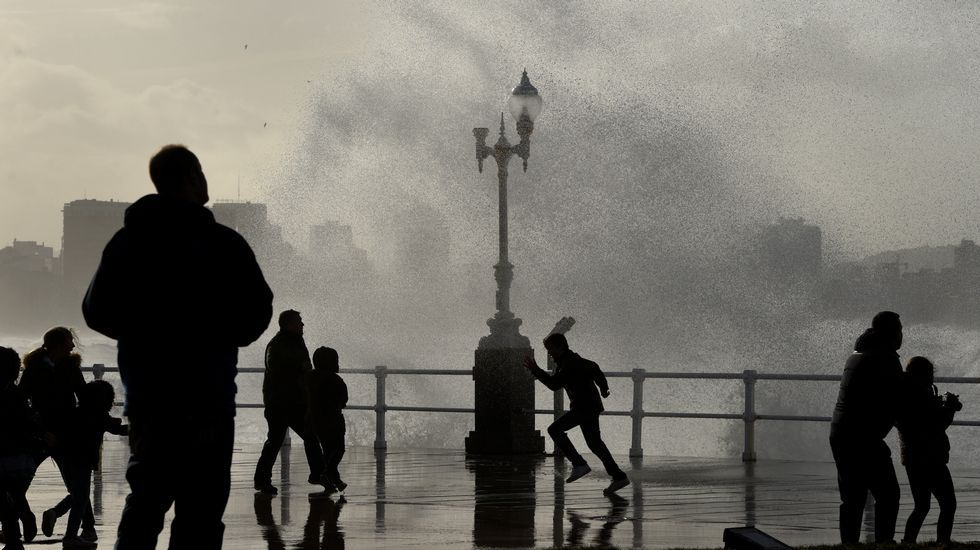 El temporal marítimo congregó a multitud de vecinos en el Muro de San Lorenzo, en Gijón