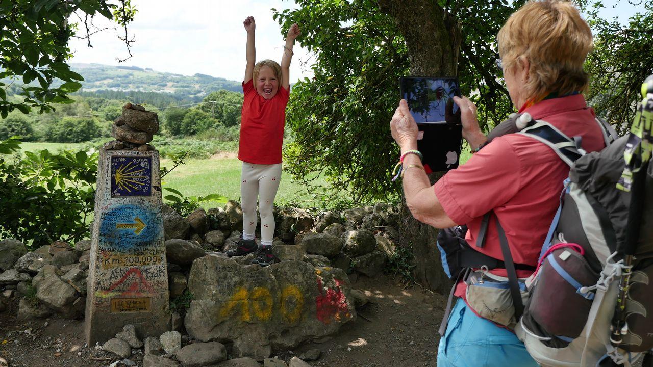 .Alegría de abuela y nieta en el mojón que señala que faltan 100 kilómetros para llegar a Santiago