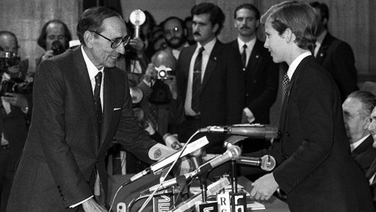 Un grupo de pasajeros consulta los vuelos en el Aeropuerto de Asturias.El príncipe Felipe, hoy Felipe VI, entrega el galardón de las Letras a Miguel Delibes