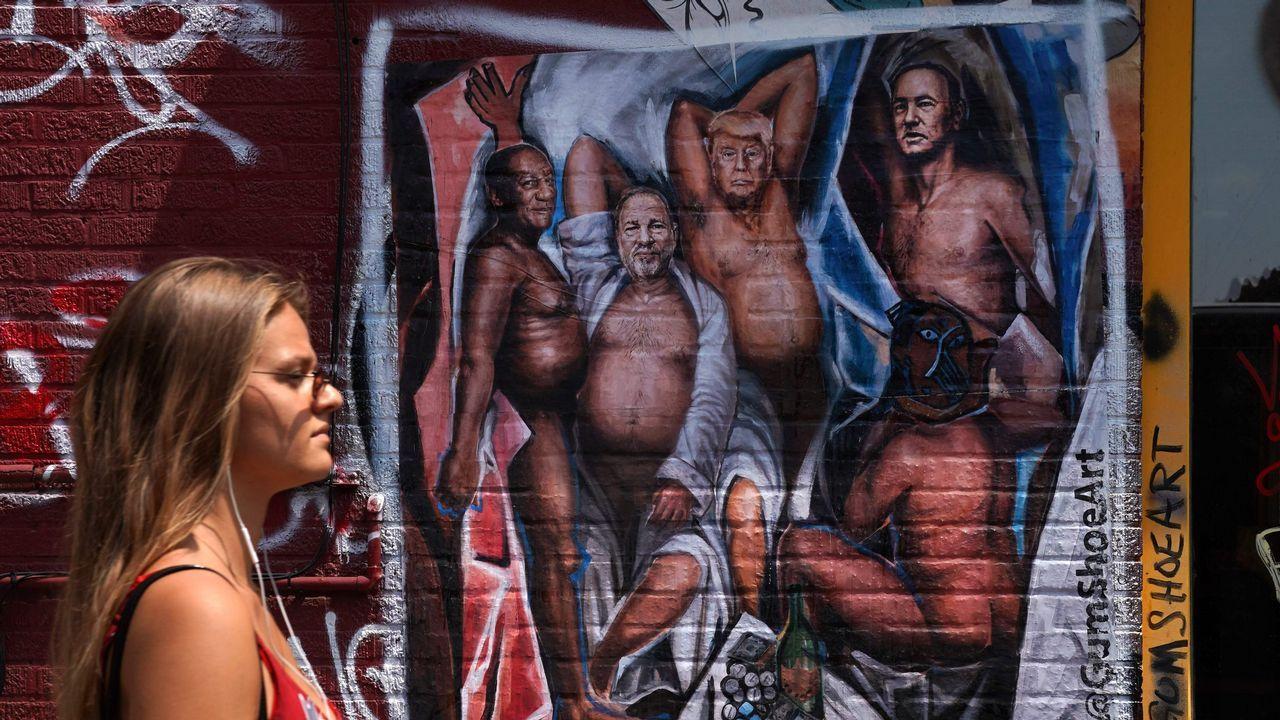 Una mujer camina por delante de un graffiti en Brooklyn que retrata a Trump, Weinstein, Bill Cosby y Kevin Spacey