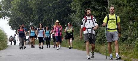 .Cuatro peregrinos cruzan la Praza 8 de Marzo de Cee en su caminata hacia Fisterra.