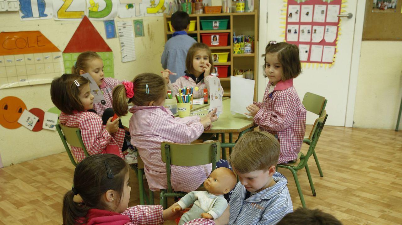 Arriba, los alumnos de 4 años colocan unas pegatinas en las fichas mientras los de 5, en primer plano, juegan.
