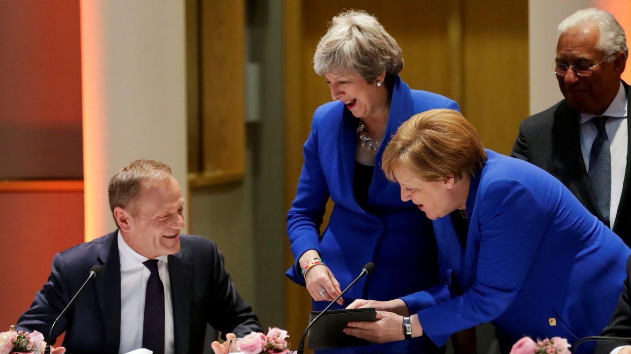 Protestas de grupos ecologistas en Londres.Tusk, May y Merkel observan una tableta, al lado del portugués Costa, en la cumbre