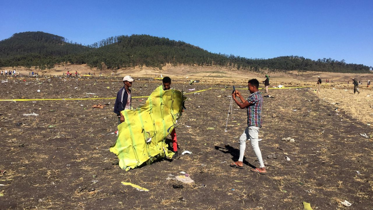 Un civil sujeta parte del fuselaje del avión accidentado mientras es fotografiado