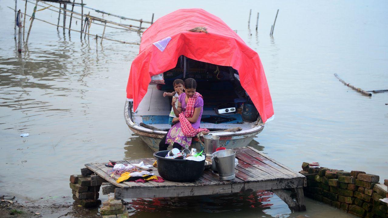 Una mujer india y un niño, en un bote con sus pertenencias, antes de mudarse a tierra más seca después de las inundaciones en las orillas del río Ganges