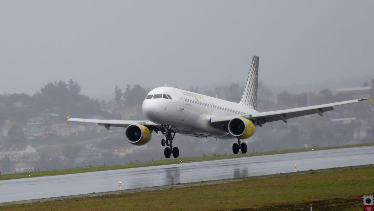 Un grupo de pasajeros consulta los vuelos en el Aeropuerto de Asturias.Un avión de Vueling