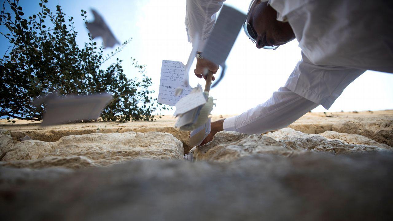 .Un trabajador saca notas de las grietas en el Muro de las Lamentaciones en la Ciudad Vieja de Jerusalén, como es habitual antes del año nuevo judío