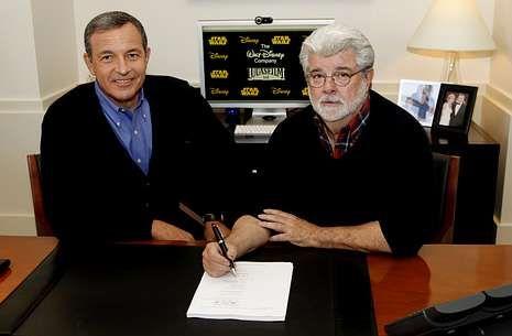 Iger, a la izquierda, firma junto con Lucas el acuerdo de venta de su empresa a Disney.