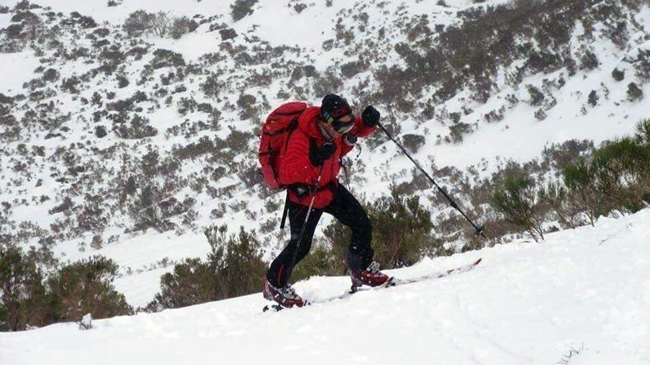Los esquiadores disfrutan de la nieve con la estación de esquí de Valgrande-Pajares al fondo.Un esquiador de montaña