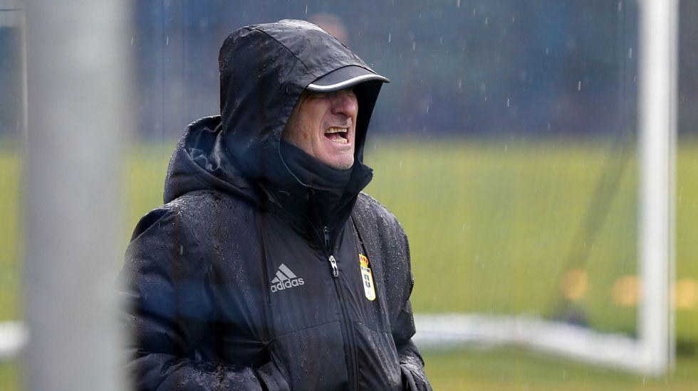 El entrenador del Real Oviedo, Juan Antonio Anquela, bajo la lluvia durante un entrenamiento del equipo en El Requexón.