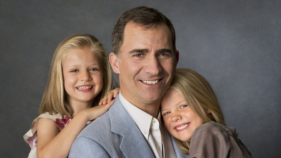 .Las infantas Leonor y Sofía aparecen abrazadas a su padre el príncipe Felipe, en una fotografía tomada por Cristina García Rodero que forma parte del reportaje realizado en la residencia de los Príncipes de Asturias el pasado 1 de agosto de 2012.