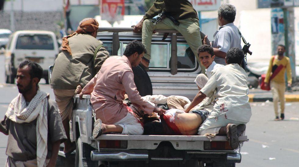 .Civiles evacúan a los heridos en los bombardeos saudíes sobre el puerto de Adén.