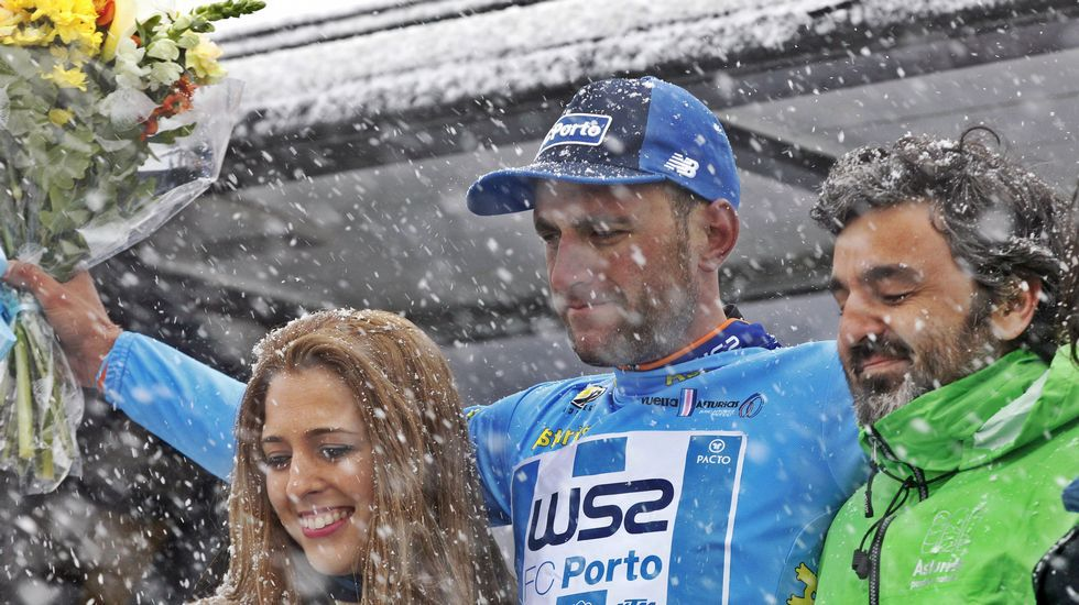 El ciclista Raúl Alarcón, del equipo W52/FC Porto, con el maillot azul de líder de la clasificación general en el podio del Alto del Acebo, donde está nevando, tras arrebatarle el liderazgo al colombiano Weimar Roldán, del Medellín en la segunda etapa de la 60 Vuelta Ciclista a Asturias, disputada entre Soto de Rivera y Cangas del Narcea