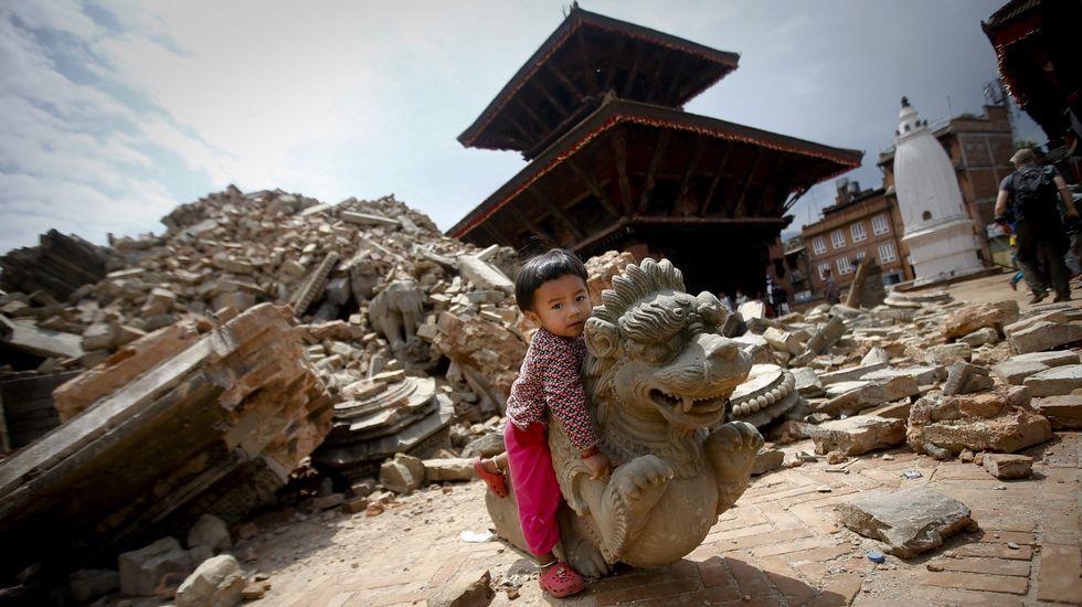 Una niña juega con una estatua caída en la plaza de Bhaktapur, en Katmandú, uno de los palacios reales situados frente a las tres plazas Durbar.