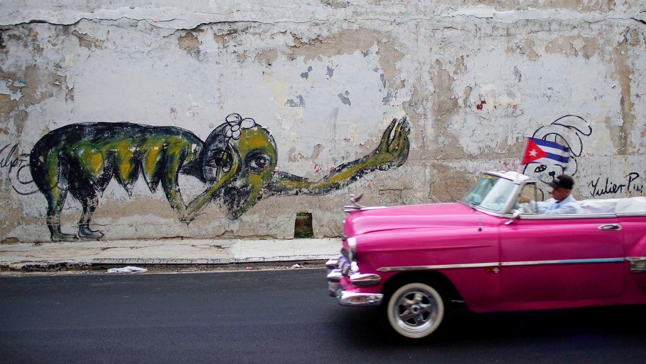 Un coche vintage pasa por una pintada del artista cubano Yulier Rodriguez en La Habana, Cuba