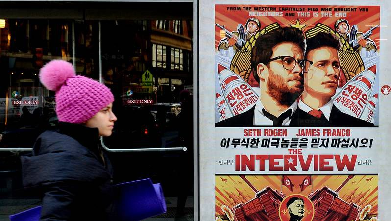 Dos trabajadores retiran un gran cartel en Hollywood que anunciaba el estreno de «The Interview», película cancelada por Sony.