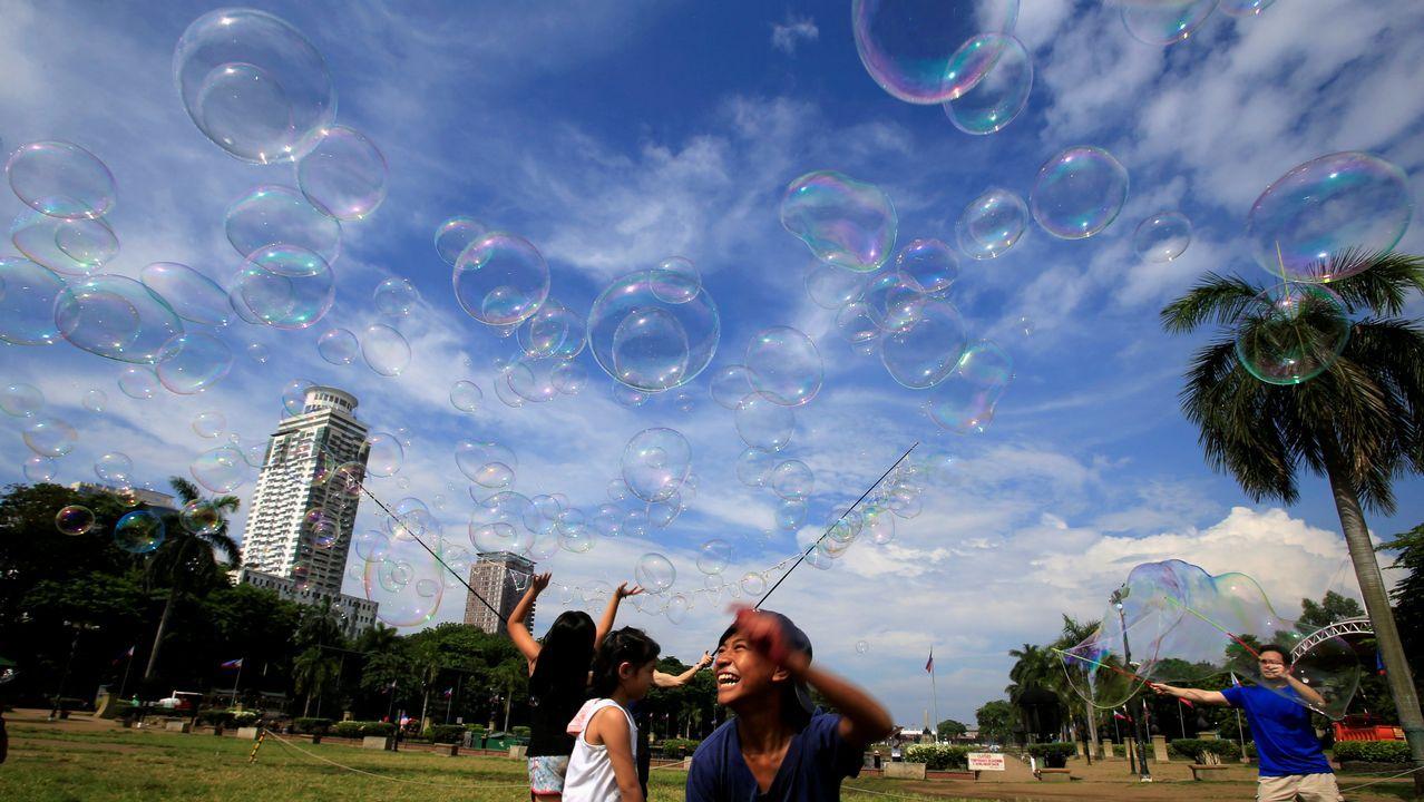 Un grupo de niños juegan con pompas de jabón en un parque de Luneta, en Manila (Filipinas)