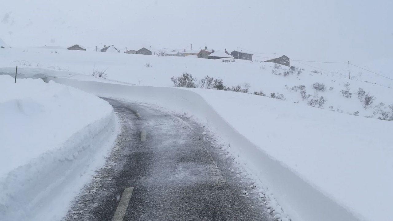 Carretera abierta alrededor de la nieve en Somiedo.Una pareja se saca una foto entre la nieve en Pajares
