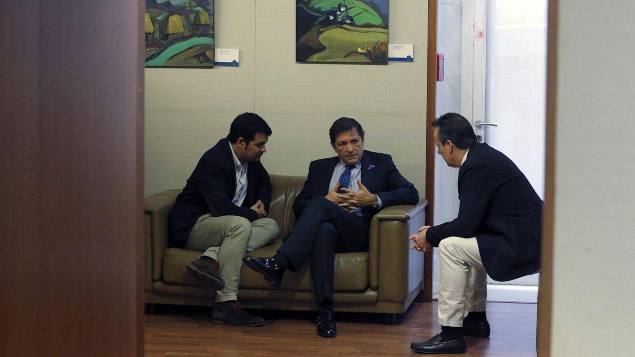 Un grupo de pasajeros consulta los vuelos en el Aeropuerto de Asturias.Nino Torre, Javier Fernández y Marcelino Marcos