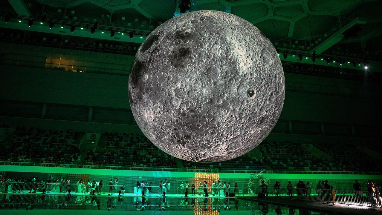 .Visitantes contemplan una escultura que representa a la Luna, del artista británico Luke Jerram, en el Centro Acuático Nacional de Pekín (China) con motivo de la celebración del Qi Xi o día chino del amor