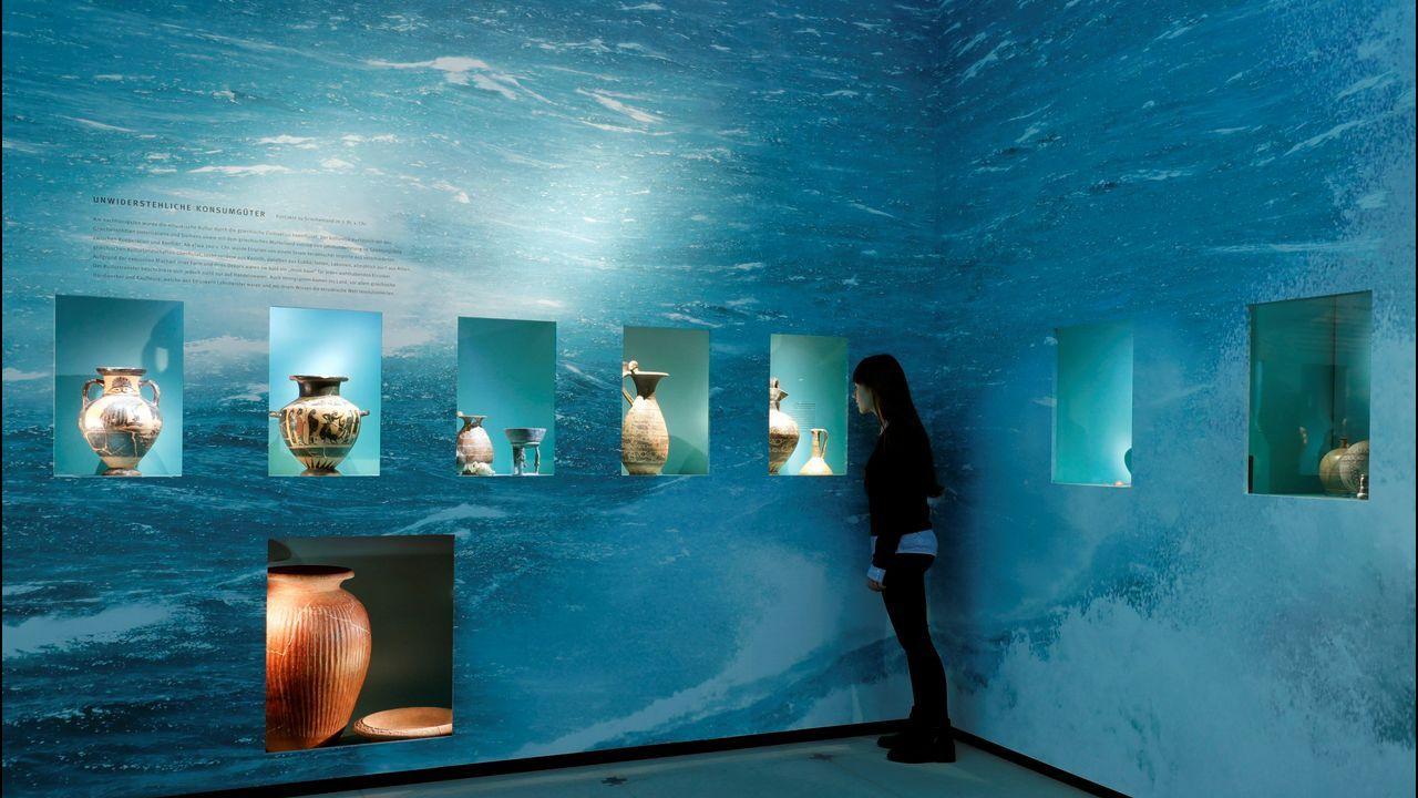 Una joven observa varias de las piezas que forman parte de la exposición «Los etruscos» en Alemania
