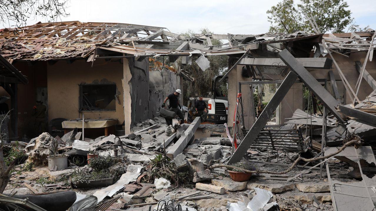 Policías inspeccionan una casa dañada tras impactar un cohete lanzado desde la Franja de Gaza en la comunidad de Mishemeret, en la región central de Israel