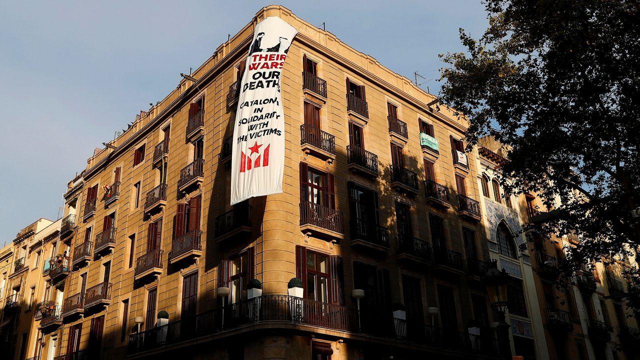 El movimiento soberanista ha colgado una segunda pancarta en la fachada de un edificio de La Rambla de Barcelona, donde en breve se celebrará una ofrenda floral a las víctimas de los atentados del 17A, en la que puede verse una imagen del Rey Felipe VI y del de Arabia Saudí estrechándose las manos.
