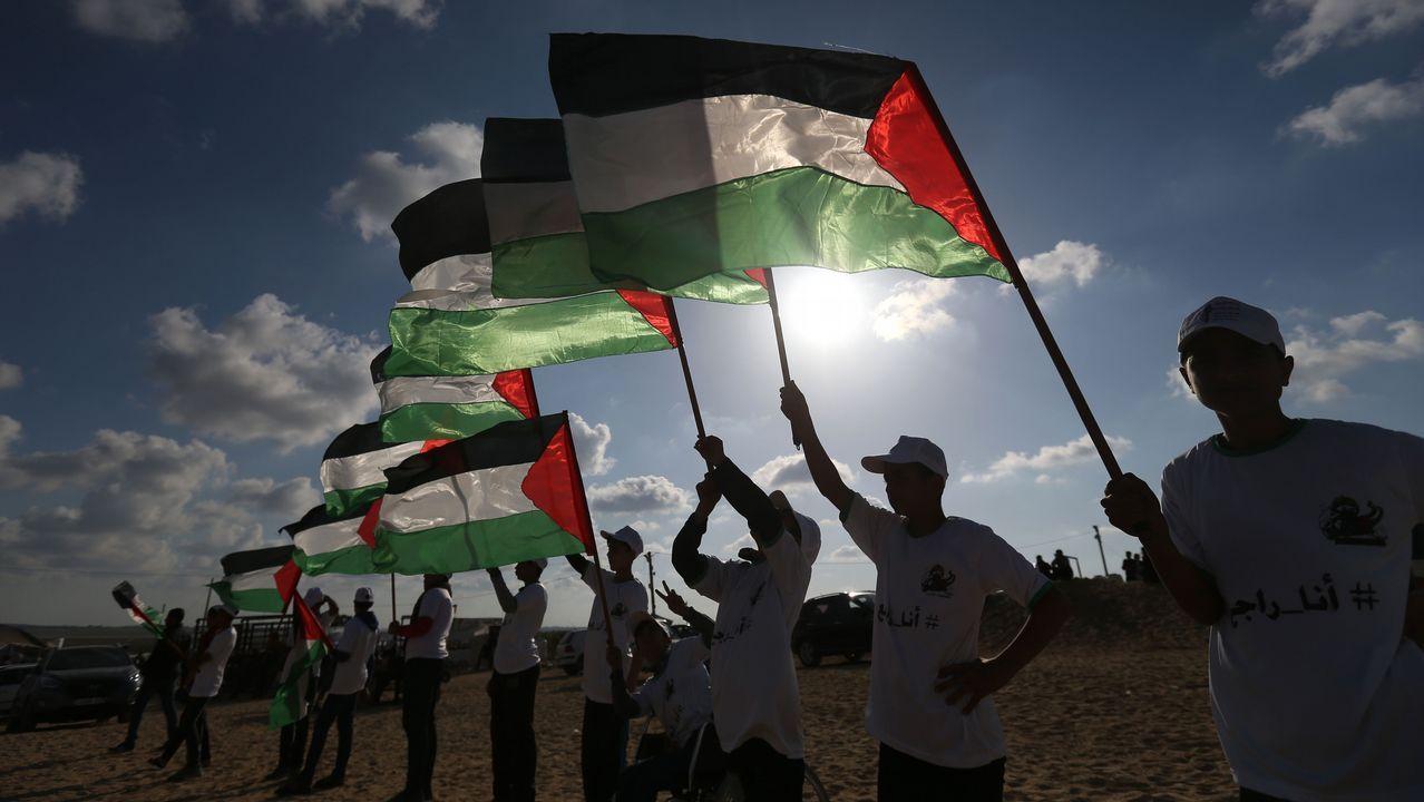 Palestinos sostienen su bandera nacional este 10 de abril en el sitio de las protestas en la frontera con Israel al este de Jabalia en el norte de la Franja de Gaza. La cerca fronteriza entre el enclave palestino e Israel se ha convertido en el telón de fondo de las manifestaciones masivas de Gaza que conducen a enfrentamientos mortales