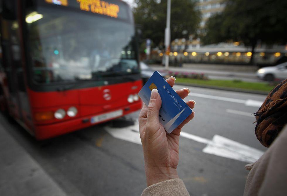 Una usuaria espera la llegada del bus con su tarjeta Millennium en la mano.