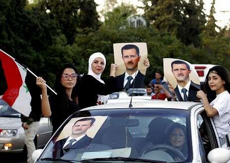 <span lang= es-es >Al Asad festeja su cumpleaños.</span> Seguidores del presidente sirio celebran el 48.º aniversario de Al Asad en las calles de Damasco, un auténtico acto de propaganda del régimen propiciado por una web.