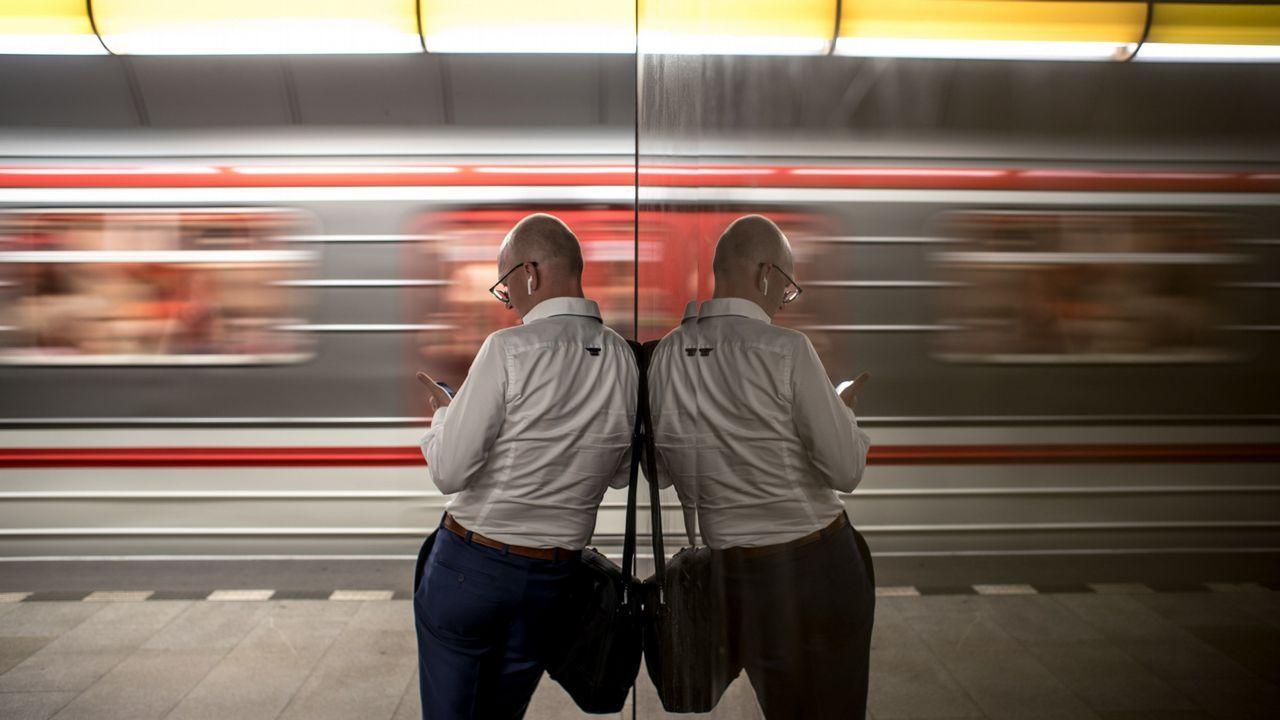 Hombre reflejado en un andén de la estación de metro de Praga