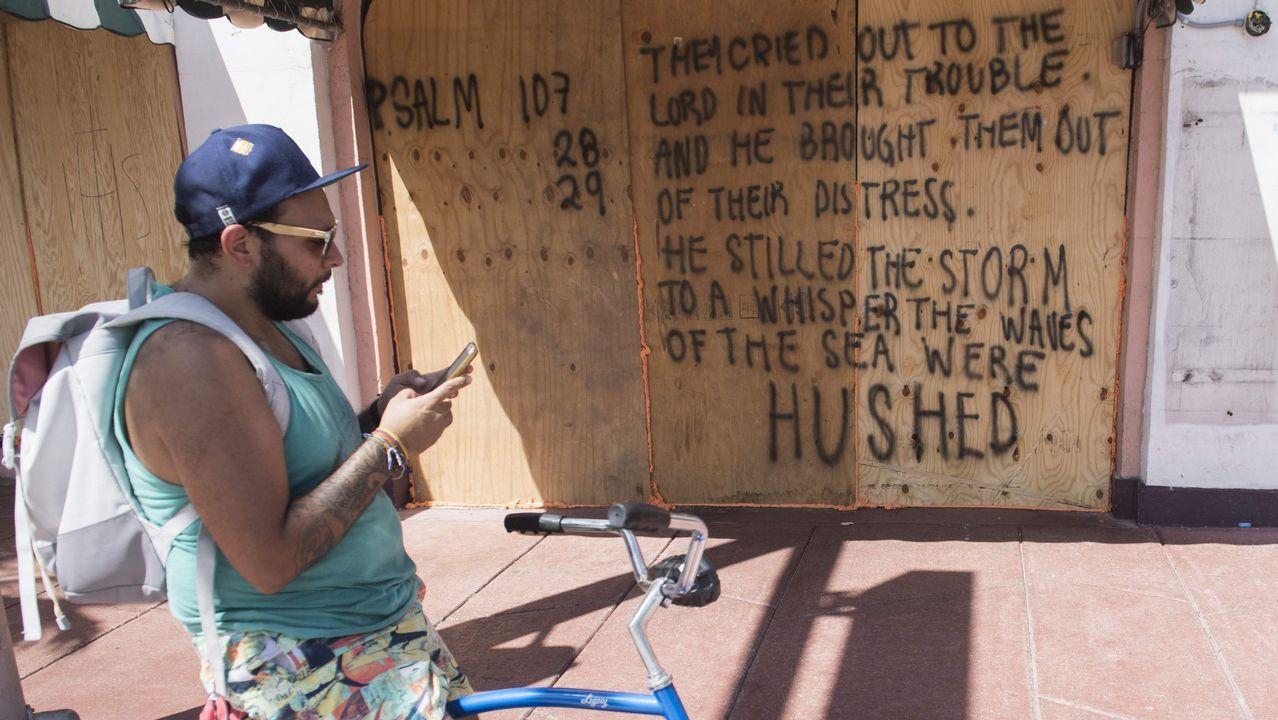 Un hombre utiliza su teléfono móvil ante una tienda protegida con tablones.