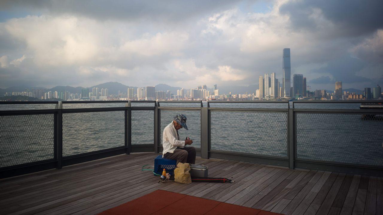 .Un anciano prepara su material de pesca en un muelle del puerto Victoria de Hong Kong's